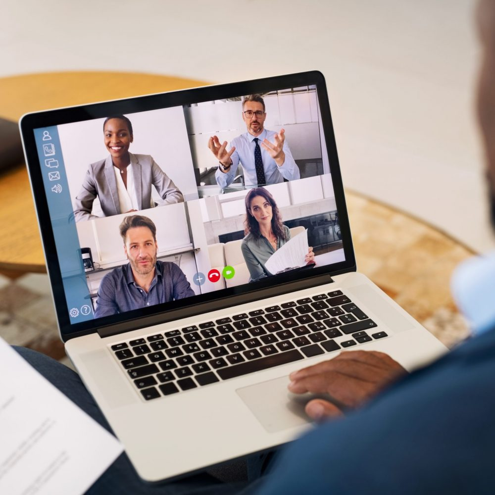 Back view of black businessman talking to his colleagues about plan in video conference from home. Multiethnic business team using laptop for a online meeting in video call during covid lockdown. Group of business people in home working discussing about the strategy.